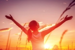 Free and happy woman raises arms against the sunset sky. Harmony and balance